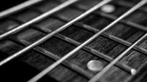 uncoated strings on a fretboard